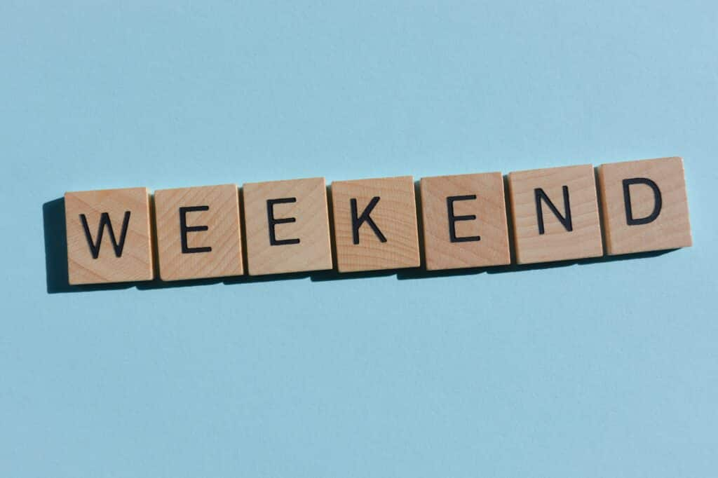 Weekend in 3D wooden alphabet letters on a blue background with copy space